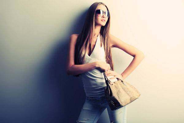 手拿包包的长发墨镜女摄影高清图片下载,高清,摄影,大图,素材,图片,人物,女人,美女,女性,外国,国外,模特,发型,头发,长发,太阳镜,墨镜,眼镜,女包,牛仔裤,靠墙,叉腰,手势,扭头