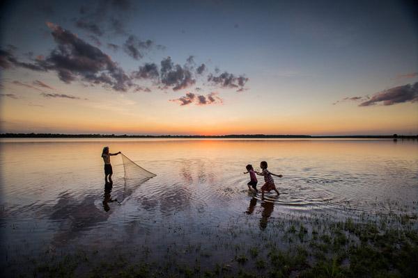 河边收网渔民